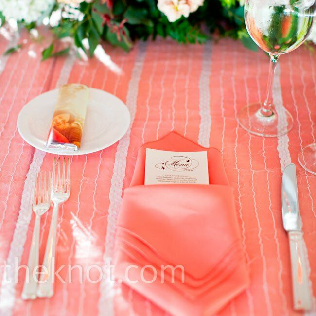 Coral linens with white overlays and satin striping rested on the tables.