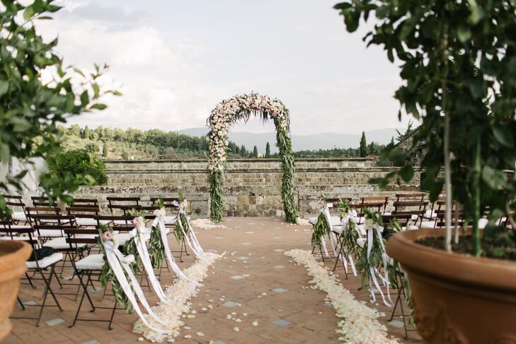 Not wanting to detract from the setting's innate beauty, the couple kept things simple when it came to the decor. The aisle was lined with ivory and blush rose petals and cascades of white ribbon, leading to a vine-covered wedding arch decorated with a garland of full pink florals.