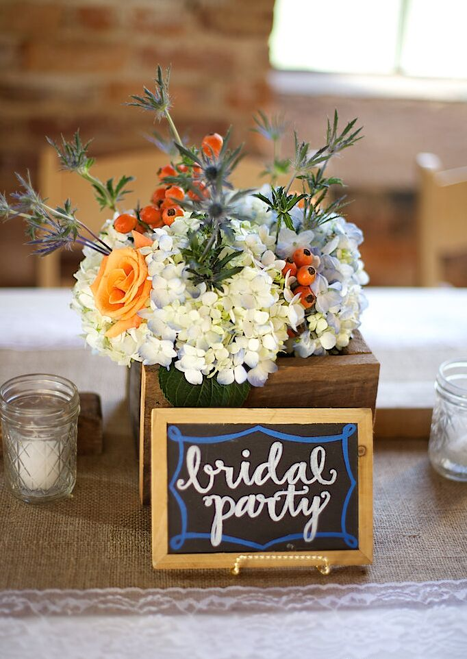 Nicole's bridal party table mimicked their bright orange bouquets with a few lighter flowers. White hydrangeas, blue sea holly, orange hypericum and green thistles filled the wooden breakaway vase. Nicole and Brandon even designated their seats with a little chalkboard sign.