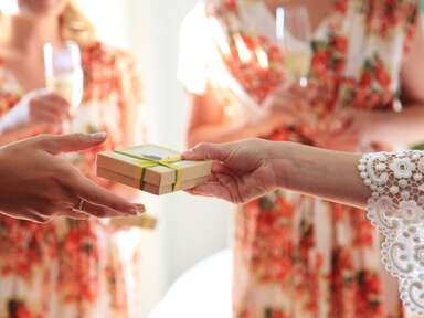 Bride giving bridesmaid gifts in wedding day robes