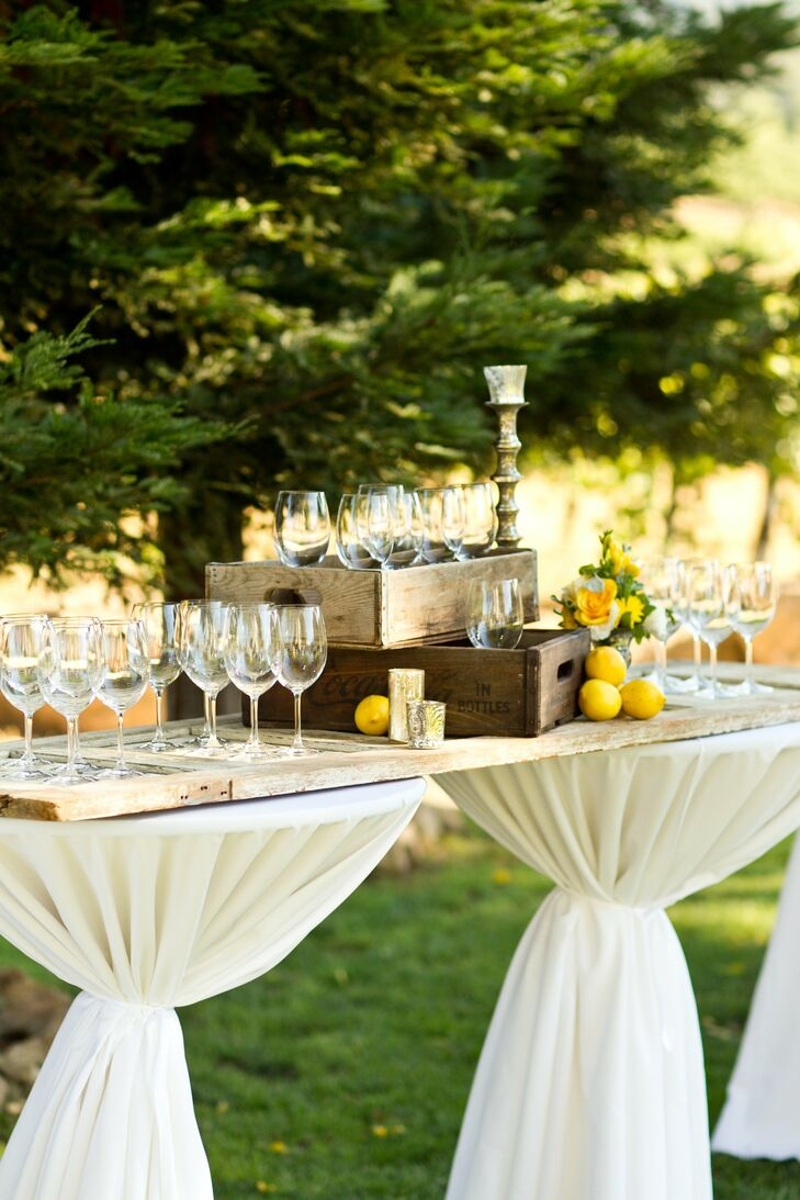 A reclaimed wooden door and vintage wood crates held wine glasses for guests during cocktail hour.