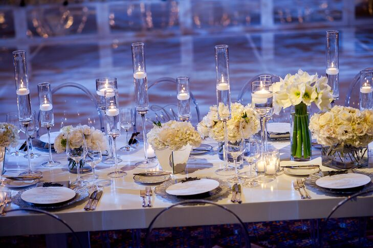 """""""Since the wedding took place in December, I decided on a modern icy winter wonderland theme,"""" Shelby says. Clear chairs, white beaded linens and an abundant array of white orchids and peonies with metallic charcoal fabric drapery created a cool modern atmosphere of winter glam."""