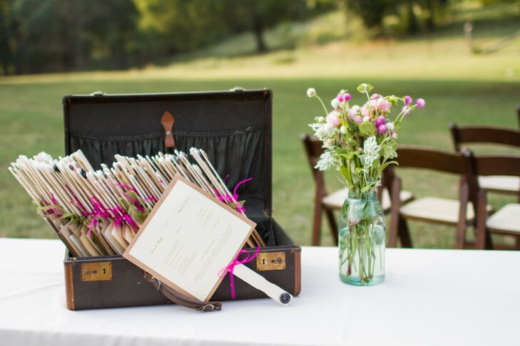 Guests stayed cool with neutral program fans accented with pink hand-tied bows to go with the bride's hot pink color palette.