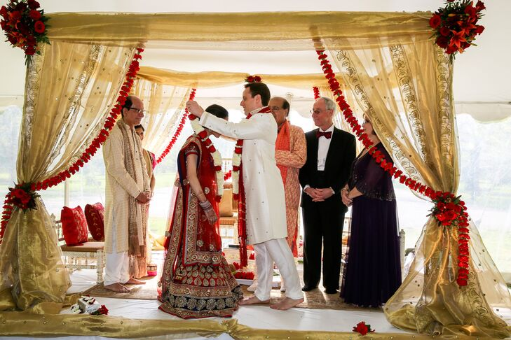 Kaveri and Michael performed a traditional Hindu marriage ceremony under a mandap, which was draped in gold linens and decorated with garlands of red carnations.