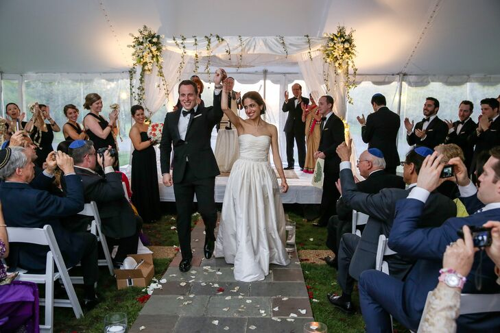 Kaveri and Michael had their Jewish ceremony under a white huppah decorated with flowers, which took place in the same tent as the Hindu ceremony.