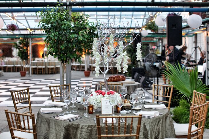 At the reception, tables were arranged with metallic tablecloths and silver centerpieces, like this silver tree adorned with garlands of white carnations.