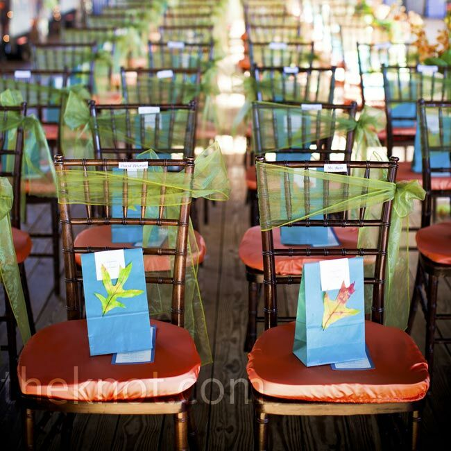 Orange cushions and green gauze sashes brought color to the wooden chiavari chairs. Bright blue gift bags decorated with leaves were set on each chair.