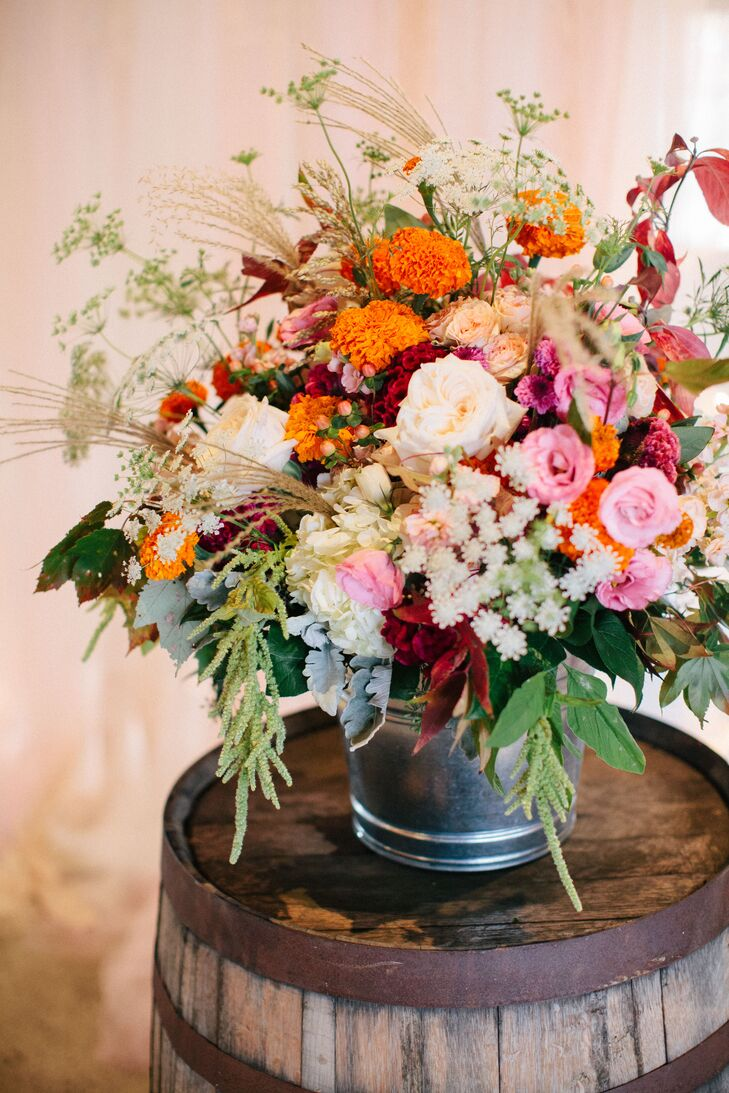 At the altar, bouquets of orange carnations, pink and ivory roses, Queen Anne's lace, red coxcomb and dusty miller were arranged on barrels.