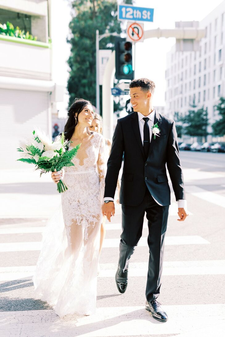 Modern Couple with Sheer Long-Sleeve Wedding Dress, Black Suit and Greenery Bouquet
