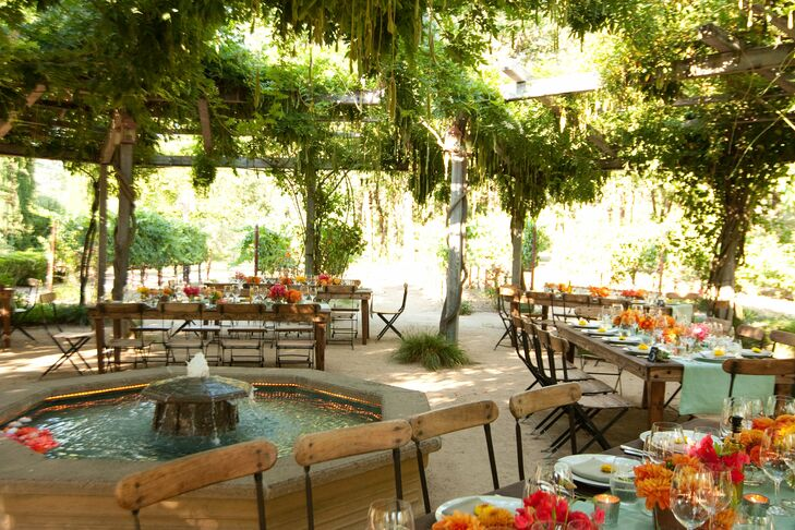 A sparkling fountain stood at the center of the Mediterranean-style living canopy where Sara and Max hosted their outdoor reception. Long wooden tables and spartan chairs looked natural in the rustic setting.