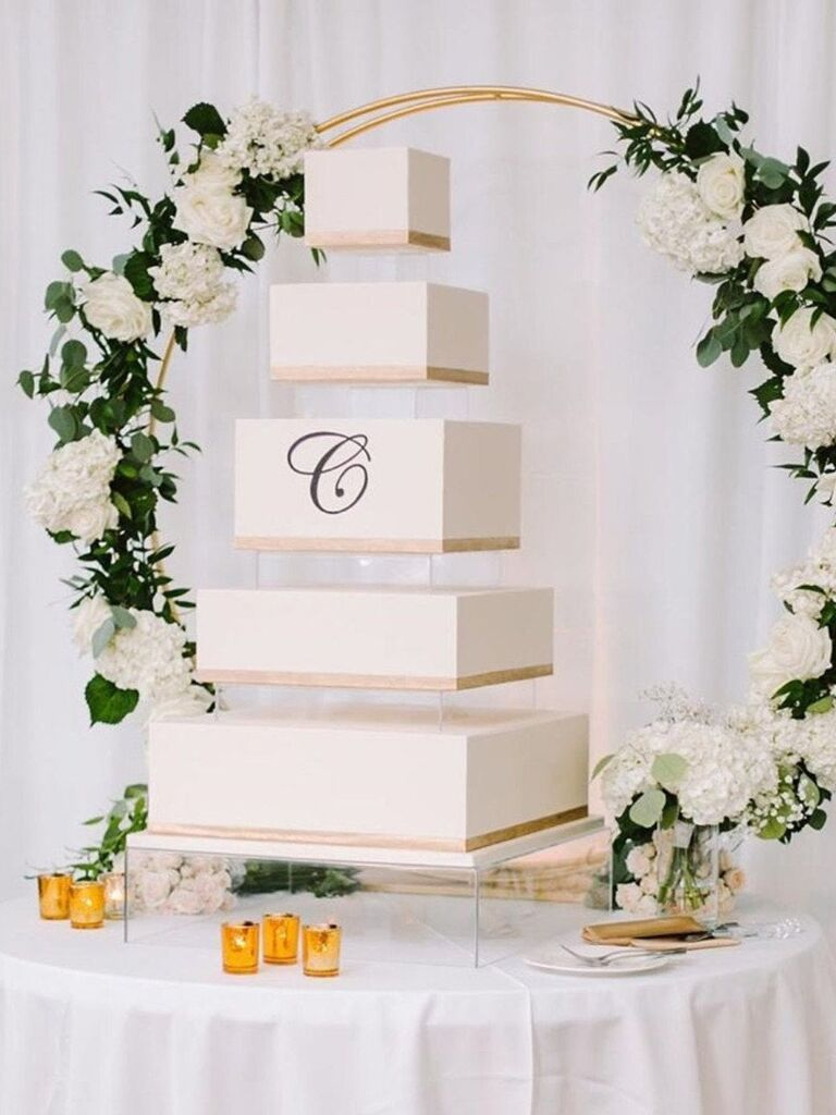 Square five-tier wedding cake with clear square acrylic cake stand and risers between each layer