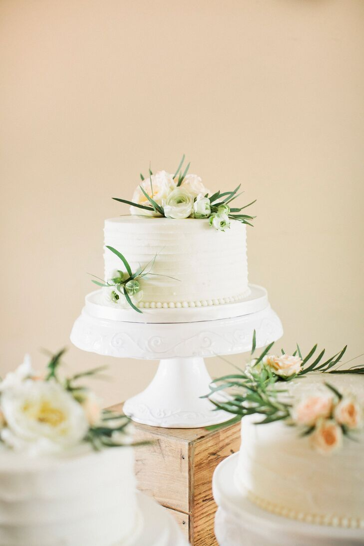 Nicole and Tom had three single-tier wedding cakes by One Belle Bakery. Inside, they were amaretto cake with amaretto custard, red velvet with cream cheese and chocolate with chocolate custard. Each cake featured a different texture with off-white buttercream frosting and fresh flowers on top.