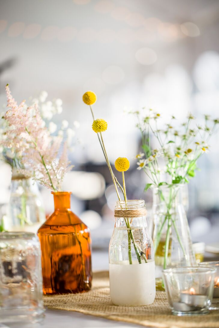 Hand-painted milk bottles and chemistry flasks were wrapped in twine and filled with wildflowers to create easy, DIY centerpieces.