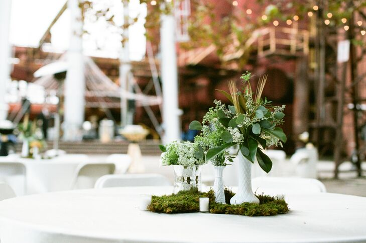 The reception tables were decorated with textured arrangements of moss, tealight candles and eucalyptus and Queen Anne's lace in white milk-glass vases.