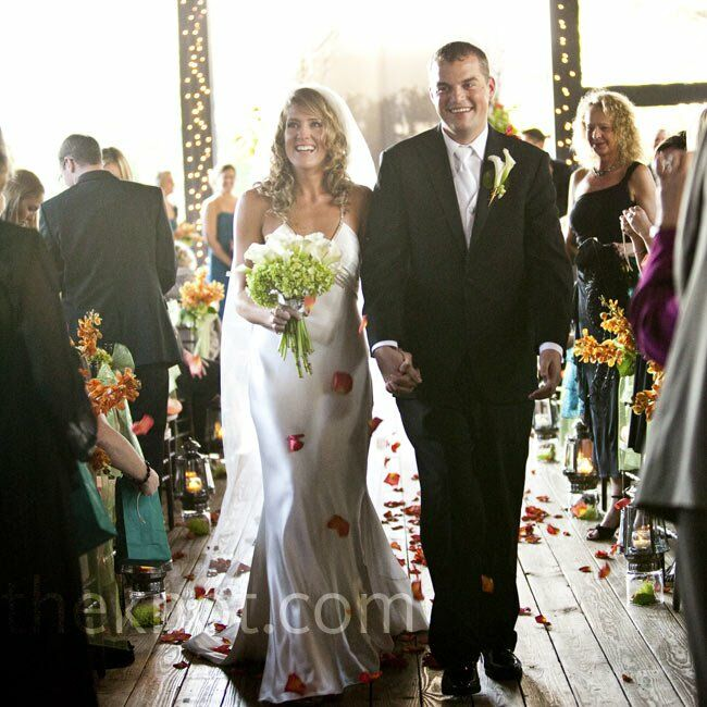 Laurie and Jason were married on the covered deck of Lioncrest. Lanterns lined the aisle and twinkle lights lit the space.