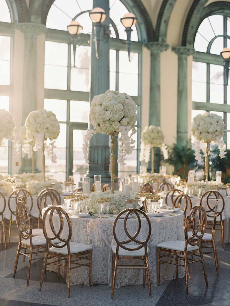 Opulent towering white floral center pieces at luxury wedding reception with gold chairs