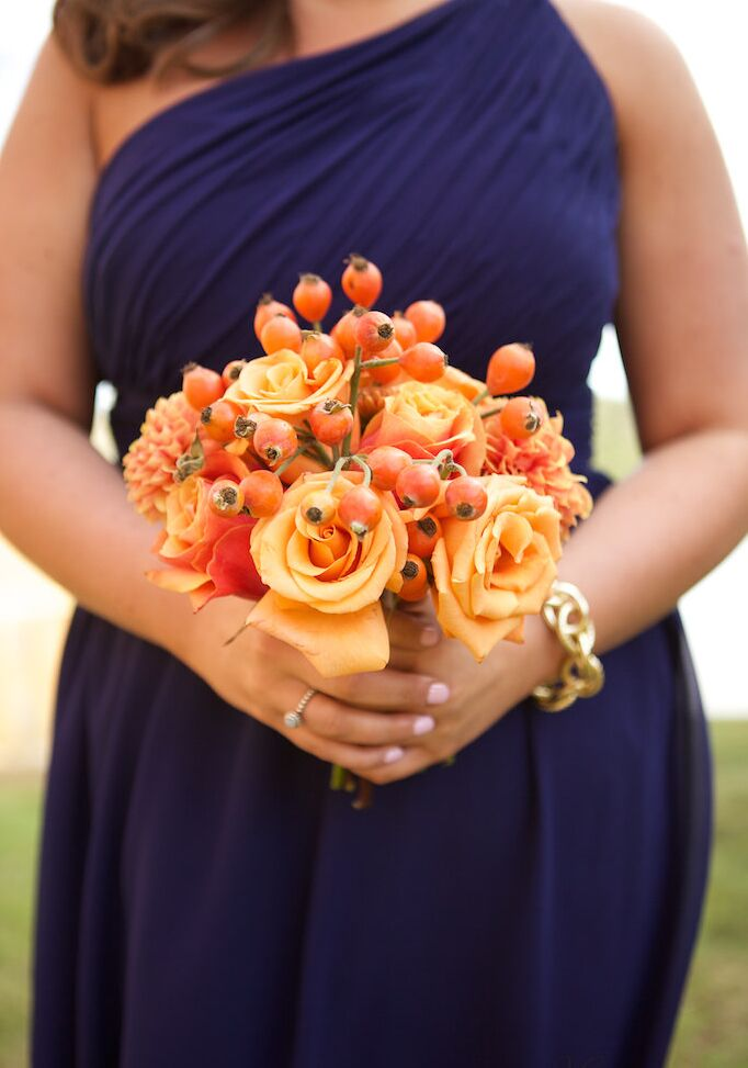 Nicole's bridesmaid bouquets matched hers with bright orange flowers. Each woman carried hypericum, roses and dahlias wrapped in burlap to bring out the rustic style.