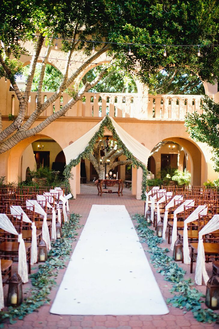 Eucalyptus leaves lined the aisle and a white drape with greenery framed the arch where Liz and Mark said their vows.