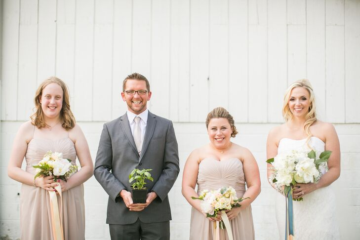 """Every member of the bridal party had a different look. Kristen's bridesman definitely stood out from the group with a gray suit, neutral tie and a basil plant as his """"bouquet!"""" Her bridesmaids wore the same dress, but one woman personalized it with added straps and a shortened, tea-length skirt. To tie things together, they both carried natural arrangements of blush peonies, greenery and orange hypericum berries from Tracey Reynolds Floral Design."""