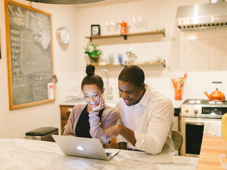 Engaged couple registering for wedding gifts on laptop at home