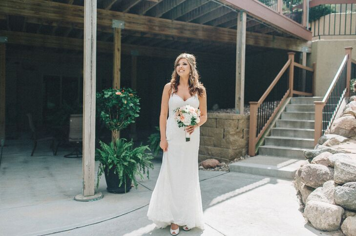 "Elayna wore a simple, lightweight ivory gown by Watters. ""The lace accents went perfectly with the simple, vintage look I was going for,"" she says."