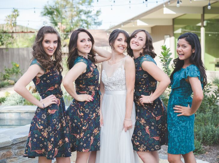 Beth stood with her bridesmaids, who wore navy blue knee-length dresses accented with floral designs that went along with the retro look of the wedding.
