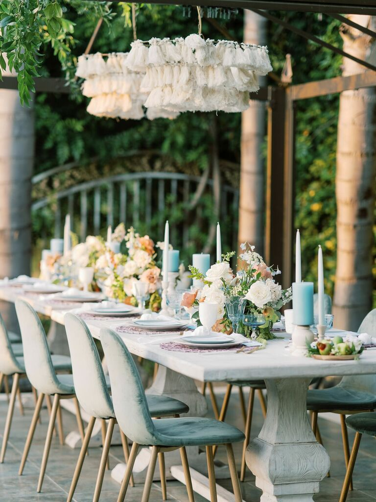 Beach reception tablescape with blue velvet chairs, blue candles and white cloth chandeliers