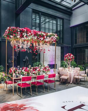 Glam Reception Table With Chandeliers and Flowers Hanging From Above