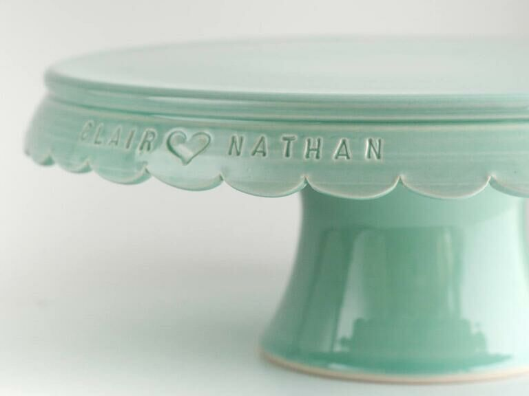 Mint green vintage-style wedding cake stand engraved with couple's names