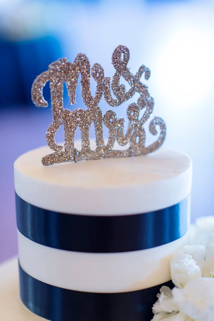 "This triple-layer white cake was decorated in black ribbon, blush roses and white peonies and topped with a gold-glitter ""Mr. & Mrs."" sign. Each layer featured a different flavor: chocolate eclair, vanilla cake with chocolate mousse filling, and vanilla cake with raspberry filling."