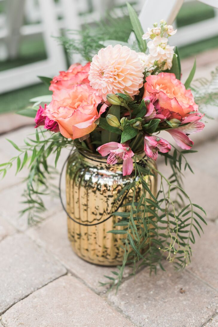 Gold vases were filled with bright pink and coral dahlias and rose blossoms and placed down the aisle at the outdoor garden ceremony at San Diego Botanic Garden in Encinitas, California.