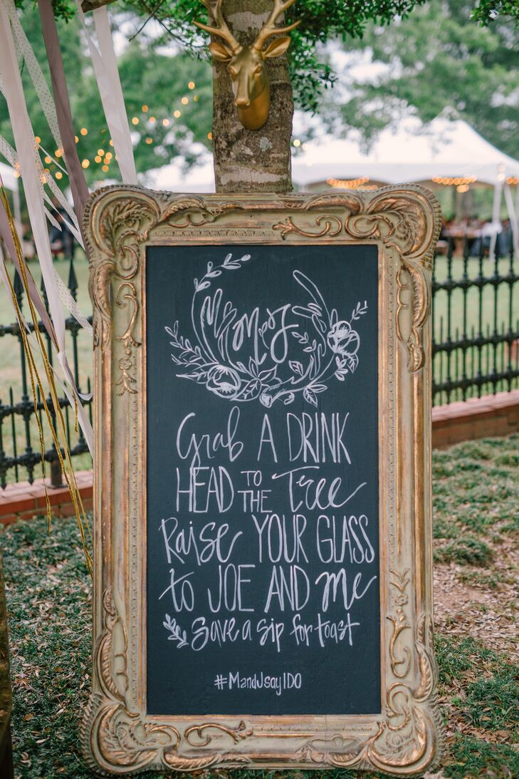 """Before """"I do,"""" a gold-framed chalkboard greeted guests with a message: """"Grab a drink, head to the tree. Raise your glass to Joe and me!"""" At the end of the ceremony, everyone joined in a toast to the newlyweds."""