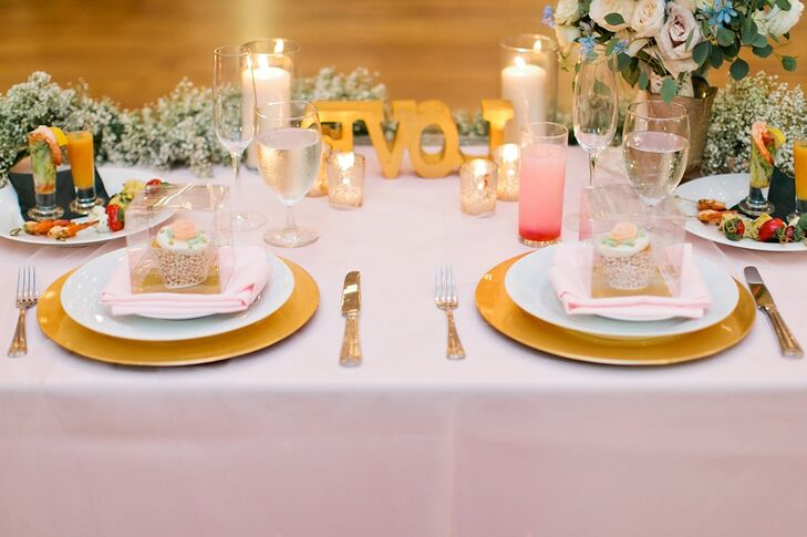 "Tables were set with small glass vases of flowers, gold chargers and candles for a soft and romantic vibe. The head table was decorated with a garland of baby's breath and a wooden block, painted gold, spelling  ""love."""