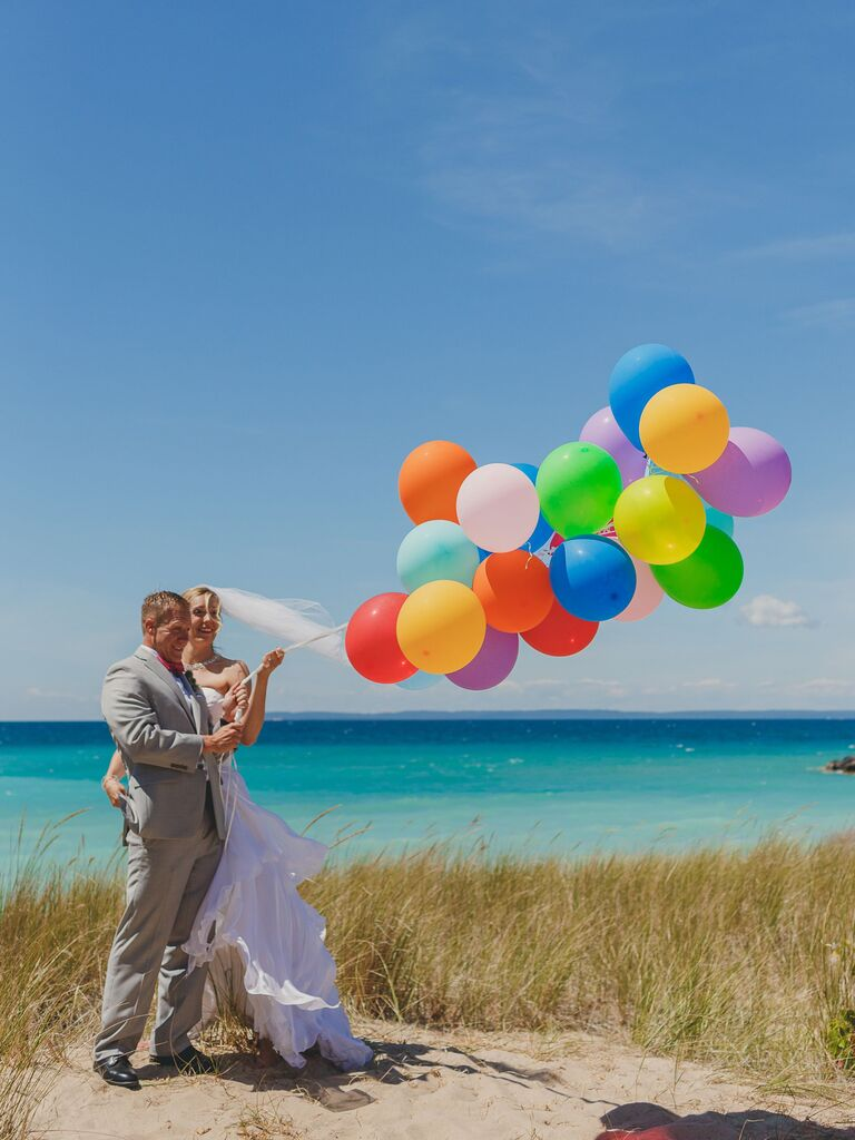 bride and groom holding colorful balloons