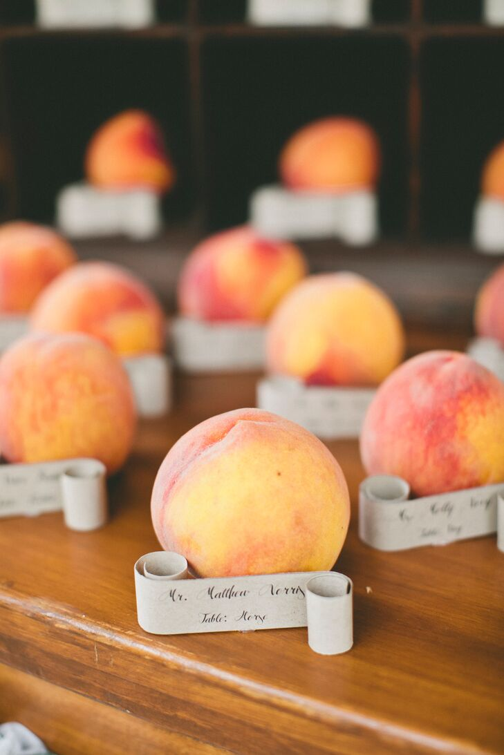 Peaches pervaded every element of the day from the bridesmaids' chiffon dresses to the peach mojito signature sips served during cocktail hour and even the escort cards that led guests to their seats. Fresh local peaches were labeled with hand-lettered scrolls bearing the names of each guest and their table name, reflecting both the peach and vintage-inspired vibes that ran through the day.