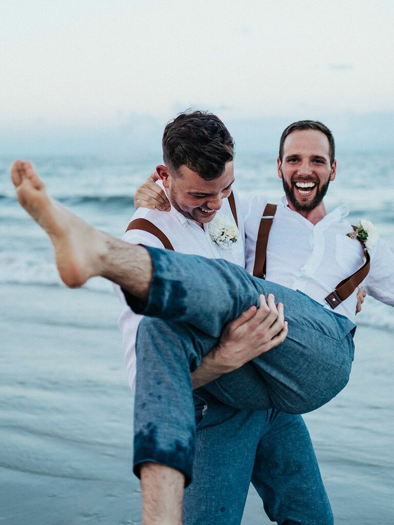 Groom laughing during summer wedding portraits on beach