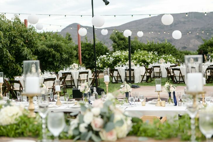 Allie and Adam's ivory-colored tables were arranged around the dance floor at their reception. The rolling mountains in the background and the white lantern string lights overhead rounded out the brilliant scene.
