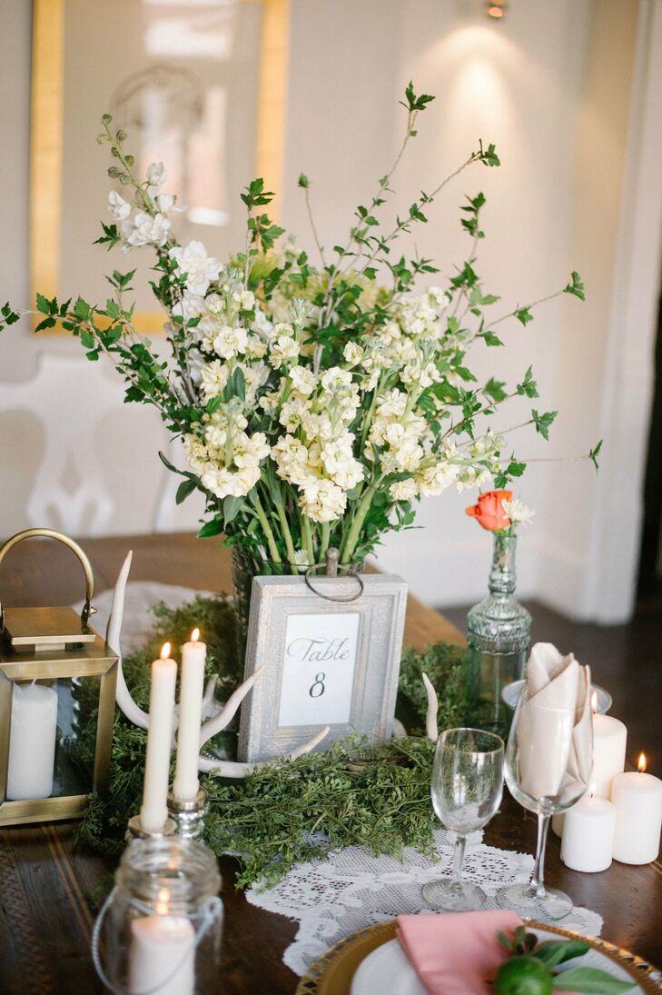 The reception tables had a romantic rustic-chic vibe with lush wreaths encircling simple arrangements of ivory stock, etched glass vases, antlers and lots of warm candlelight.