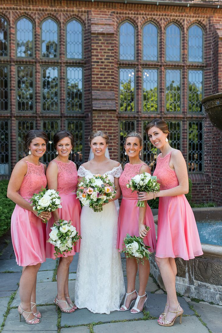 Liz's bridesmaids wore knee-length coral dresses that featured lace overlay on the bodice. They styled their hair up and wore matching drop earrings.