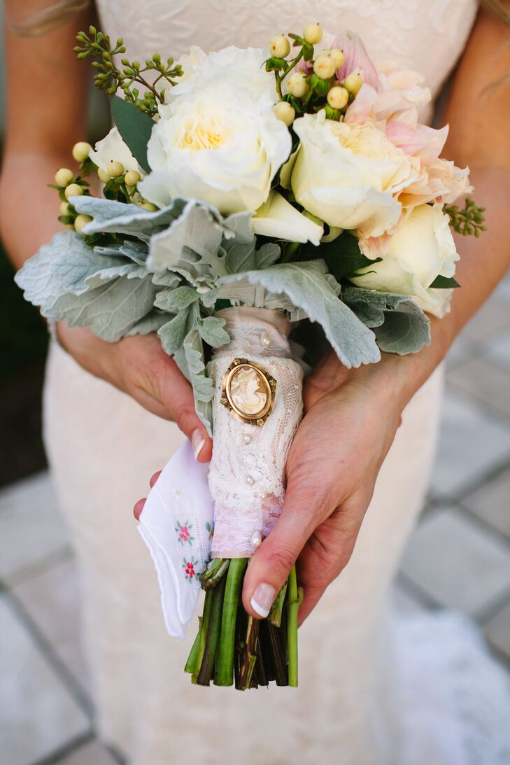 Emily carried a bouquet of pale yellow garden roses, yellow hypericum berries, dusty miller and assorted flowers in blush and white arranged by Fishers Flowers.
