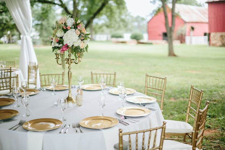 Gold candelabras filled with blush flower arrangements and matching gold chargers and chiavari chairs gave the backyard tented reception a luxurious feel.