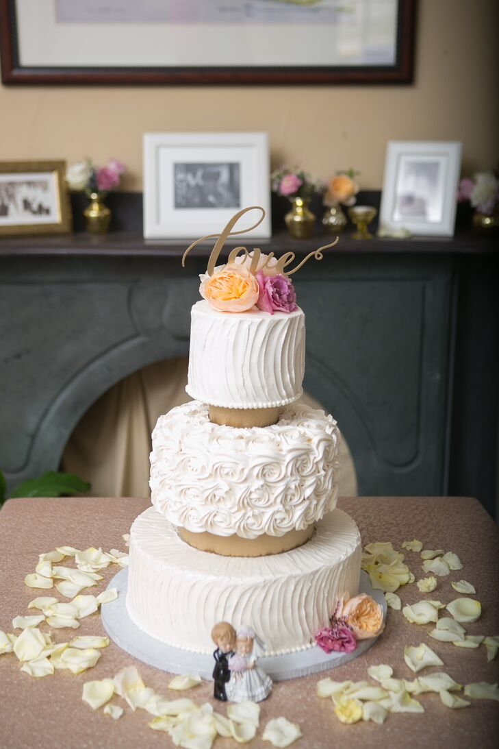 """Stella Baking contributed a sweet and simple cake. Each of its three tiers was covered with simple waves and swirls of ivory buttercream frosting. Colorful garden roses served as its topper. For a fun twist, each tier was a different flavor: lemon, red velvet and vanilla. """"This was our baker's signature wedding cake,"""" Catherine says. """"It was amazing and I will never forget it."""""""