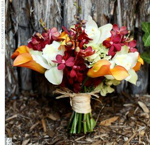 Kristin's bouquet of flame miniature calla lilies, red Mokara orchids, celadon cymbidium orchids, and antique hydrangeas was wrapped with natural raffia.