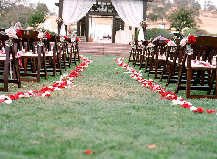 "Trails of red and white rose petals lined the aisle leading to a wooden gazebo draped with white curtains, where Marina and Vazgen exchanged vows. ""At our ceremony we kept things traditional,"" Marina says. She and Vazgen signed their marriage license on-site and partook of Communion."