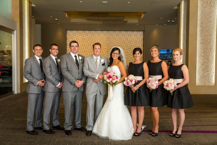Holly's bridesmaids wore short black A-line dresses with pink sashes and bows on the back along with black and white polka dot pumps.
