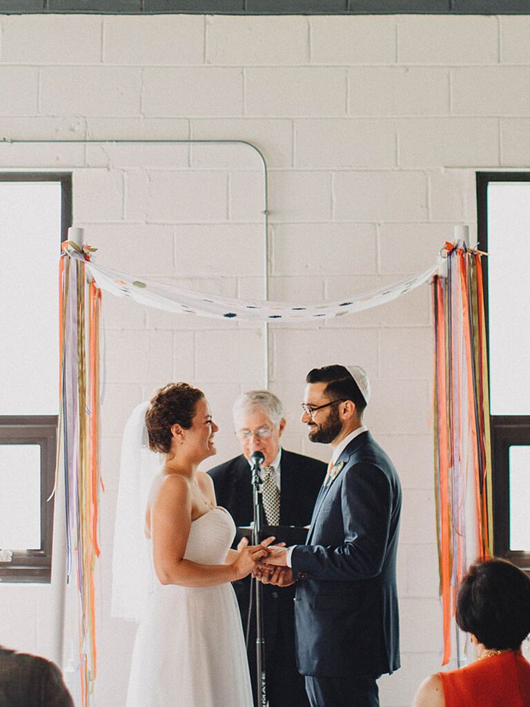 A simple DIY huppah brightens up the ceremony with colorful ribbons
