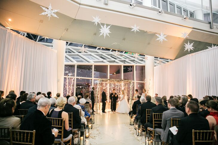 The ceremony was held at the Cire Centre Atrium, which has breathtaking views of the Philadelphia skyline. The hall was decorated with tasteful snowflakes hanging from the ceiling and wooden arch covered in string lights under which Megan and Eli were wed. The couple incorporated traditions from their Catholic and Jewish faiths into their ceremony.