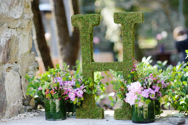 """Their garden-inspired theme went beyond landscape at the Old Mill in Rose Valley, Pennsylvania. Sarah and Tom marked the outdoor cocktail hour with various natural elements, including a chic moss marquee """"H"""" for their last name. Lush pink delphiniums, pink carnations and greenery highlighted both sides, adding to the organic atmosphere."""