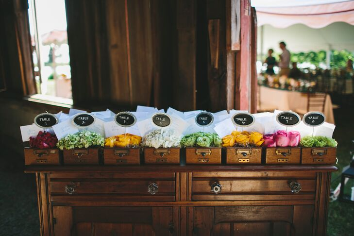 Guests found their escort cards inside the elegant wooden dresser at the reception. Numbers labeled each open drawer, filled with colorful blooms and paper with names of friends and family members that guided them to seating assignments.