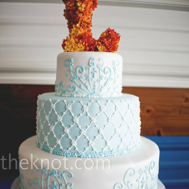 White piping and frosting decorated the cake, while orange flowers shaped into an L served as the topper.